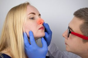 The doctor checks the swelling nose of the patient.