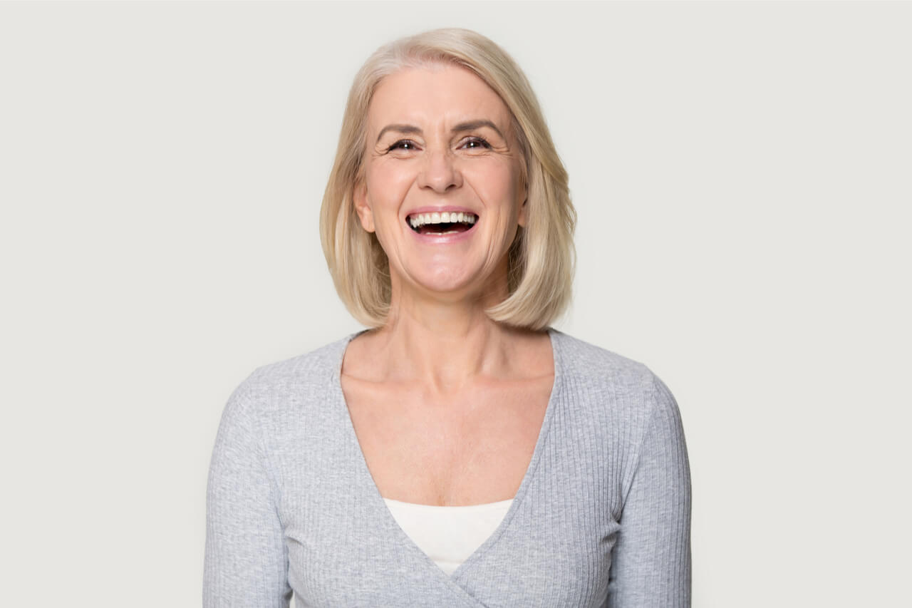The older woman has healthy and white teeth.