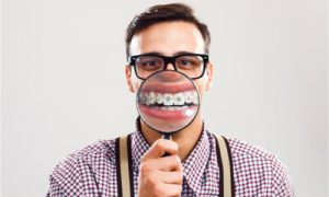 A man in glasses showing off his braces after surgery.