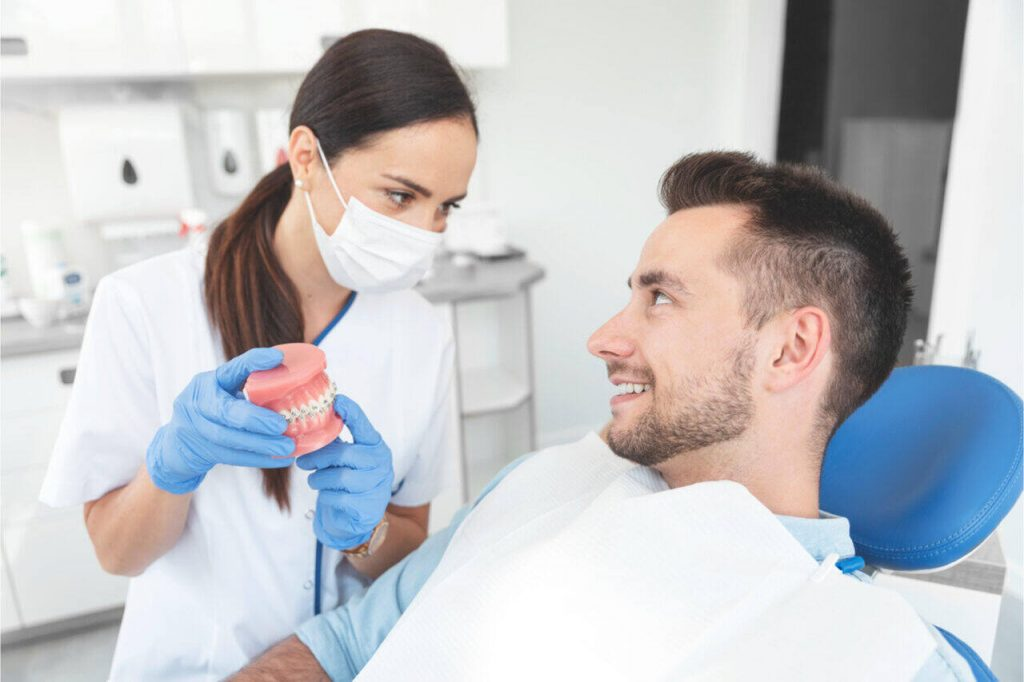 A dentist explaining to her patient about jaw surgery and braces.