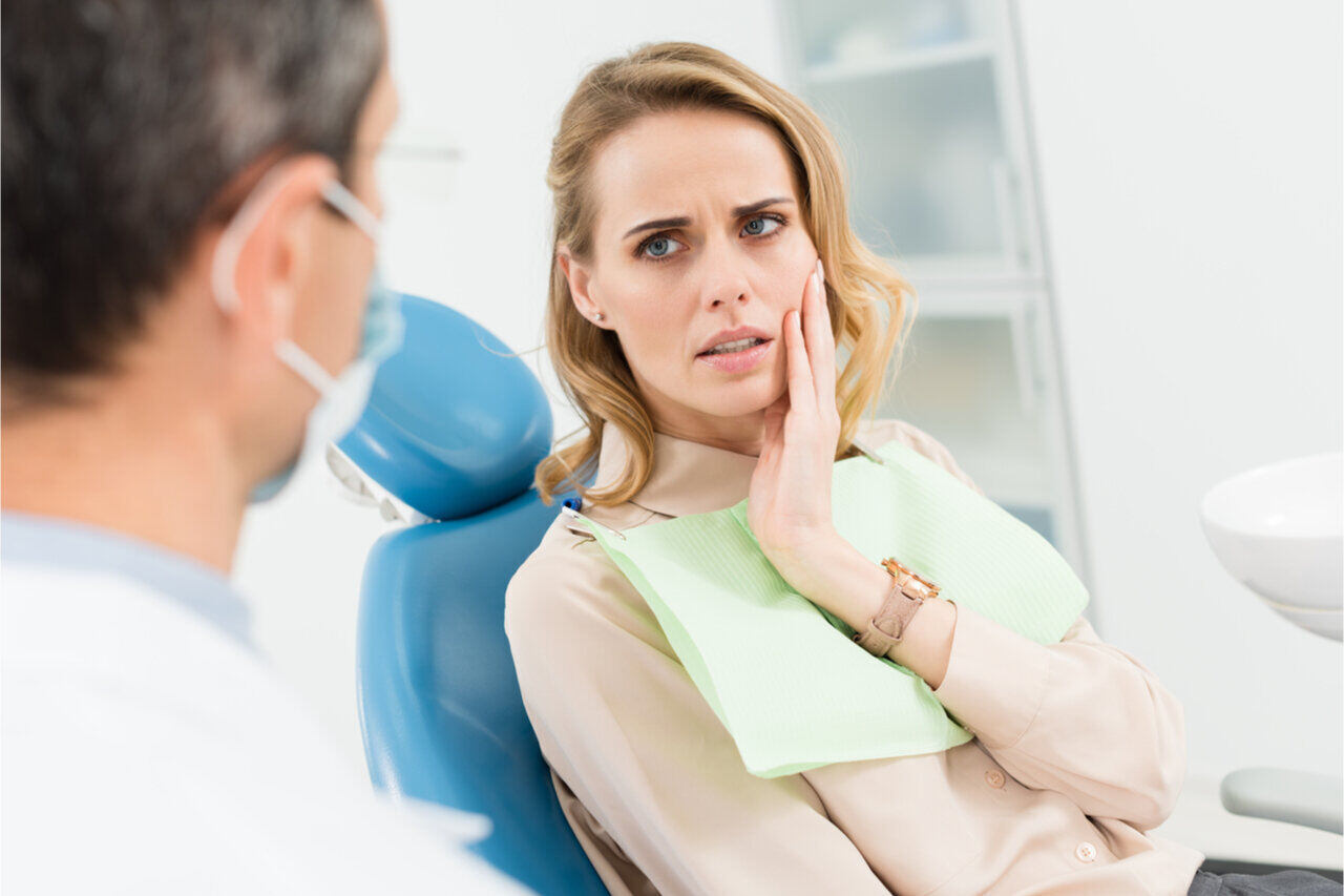 A woman asking her dentist how long does dental bone graft pain last.